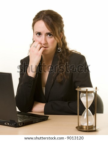 Young brunette woman working at her desk on a laptop computer staring at an old hourglass time while biting her finger with a worried expression