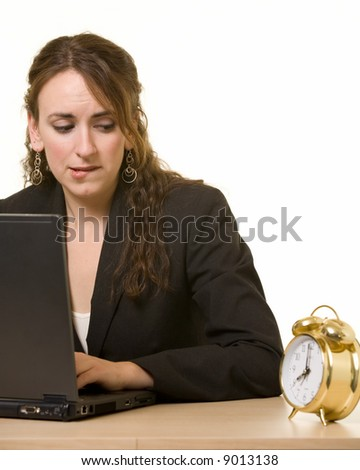Young brunette woman working at her desk on a laptop computer staring at the clock while biting her lip with a worried expression