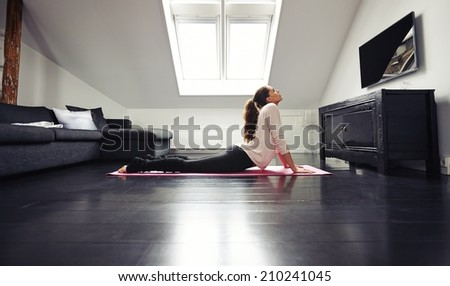 Young brunette woman working out stretching exercise on floor. Fitness female model exercising on mat at home. - stock photo