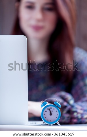 Young brunette woman working with notebook near a little alarm clock - stock photo