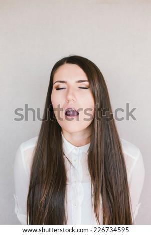 young brunette woman yawns - stock photo