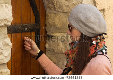 Young Brunette Women With Sunglasses Knocking On An Old Wooden Door Taken From Close-Up - stock photo