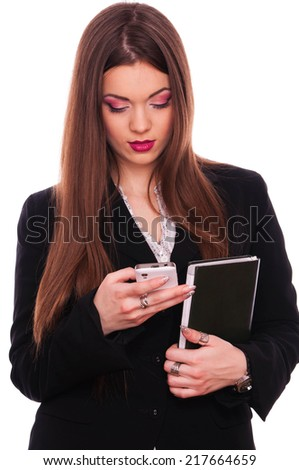 Young brunette writing message on mobile phone - stock photo