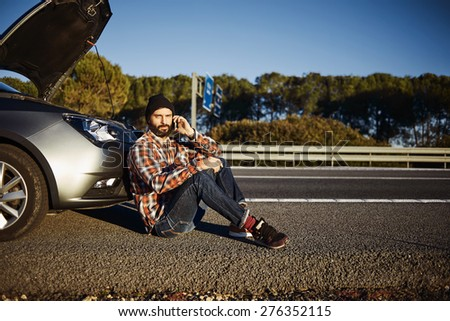 Young brutal caucasian male looking at camera. Sits near car talking on cell phone because his automobile broken. Man in sunny summer day trying to call service that they help repair car
