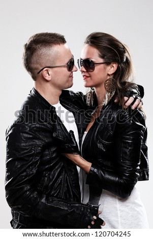 Young brutal couple in leather and sunglasses in studio