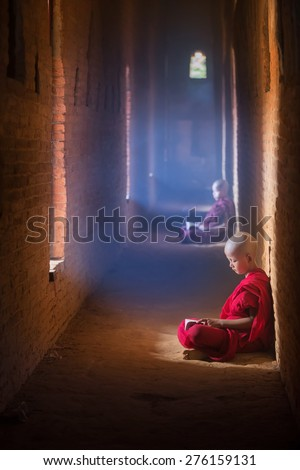 Young Buddhist monk reading and study in , sitting in pagoda inside monastery, Myanmar. - stock photo