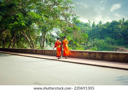 Young buddhist monks at city street. Luang Prabang, Laos travel landscape and destinations - stock photo