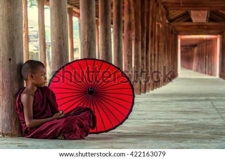 Young Buddhist novice sitting in pagoda,myanmar - stock photo