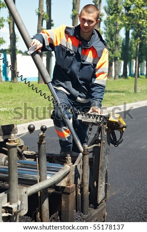 Young builder and Asphalt machine during Road street repairing works - stock photo