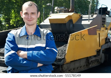 Young builder and Asphalt paver spreader at Road street repairing works - stock photo
