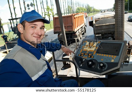 Young builder at Asphalt machine cabin during Road street repairing works - stock photo