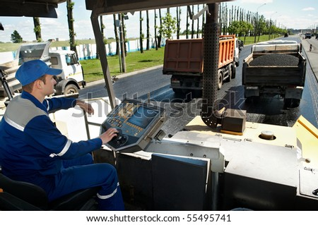 Young builder at Asphalt spreading machine cabin during Road street repairing works - stock photo