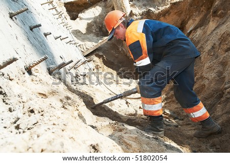 young builder at construction site working with pneumatic plugger hammer - stock photo