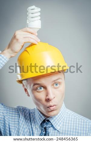 Young builder holding energy saving bulb - stock photo