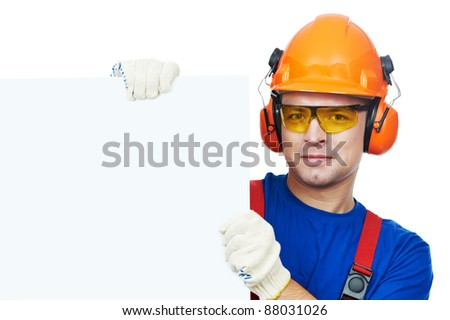 Young builder in safety equipment goggles hard hat earmuffs isolated with white empty billboard - stock photo