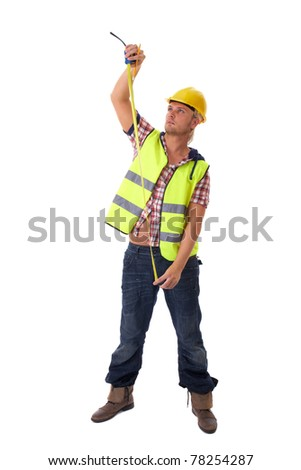 young builder in vest and yellow hardhat measure something, isolated on white background - stock photo