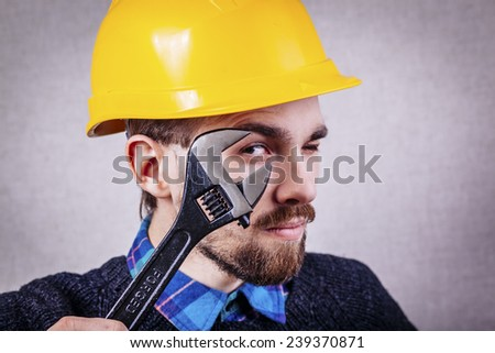 Young builder looking through a wrench