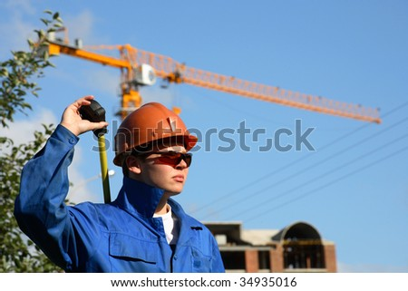 Young builder man with ruler, background crane