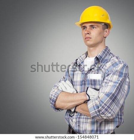Young builder on a gray background - stock photo