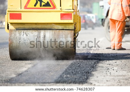 Young builder on Asphalting paver machine during Road street repairing works - stock photo