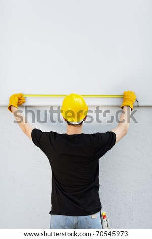 young builder with yellow tape measure on real construction site, selective focus , natural soft light - stock photo