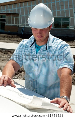 Young Building Contractor Checking The Plans To A New Commercial Building - stock photo
