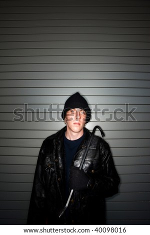 Young burglar in leather jacket with crowbar - stock photo
