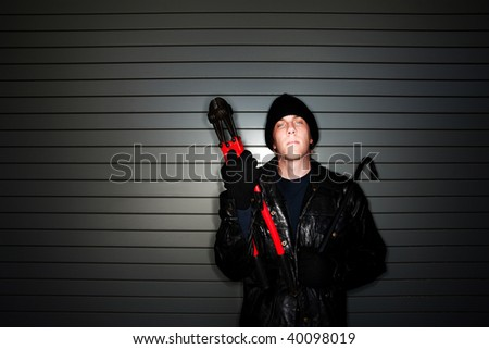 Young burglar in leather jacket with crowbar and bolt cutter - stock photo