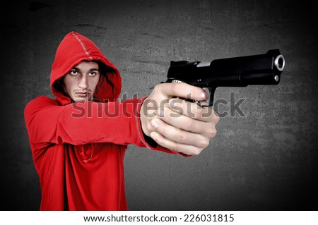 young burglar with gun in hand on a black background - stock photo