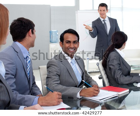 Young businesman studying a new business plan with his team in the office - stock photo