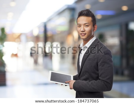 young business asian man using his tablet - stock photo