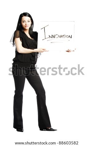Young business casual woman holding white board that says innovation - stock photo
