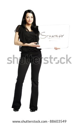 Young business casual woman holding white board that says strategy - stock photo