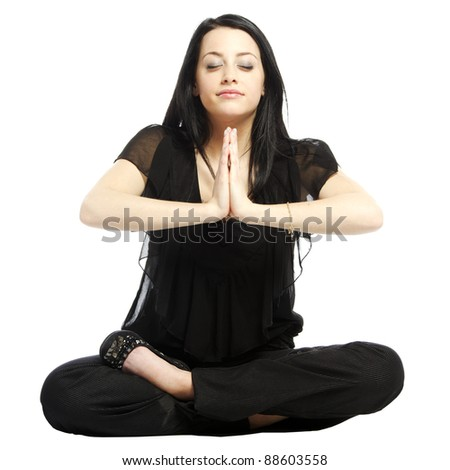 Young business casual woman in a lotus yoga position looking at camera meditating with eyes closed - stock photo