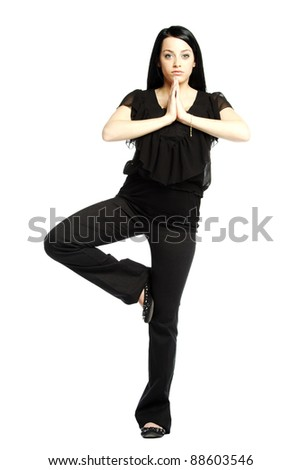 Young business casual woman in yoga position against white background - stock photo