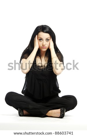 Young business casual woman sitting and worrying on white background - stock photo