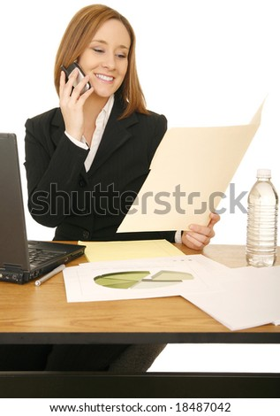 young business caucasian woman working on her desk and on the phone - stock photo
