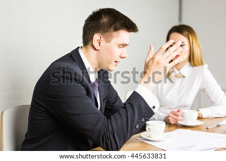 young business colleagues discussing work on a laptop computer in co-working space, corporate businesspeople - stock photo