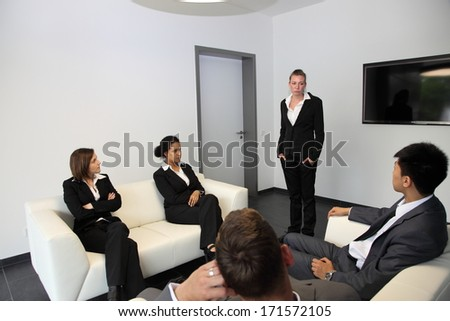 Young business colleagues in a waiting room sitting with folded arms on the sofas or standing waiting for a meeting or interview - stock photo