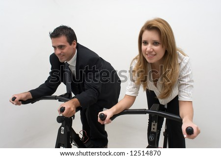 Young business colleagues riding on exercise bikes together. Horizontally framed shot with both subjects facing forward. Isolated. - stock photo