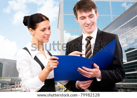 Young business colleagues working together on background a modern office building - stock photo
