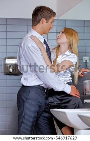 Young business couple flirting with each other at office washroom