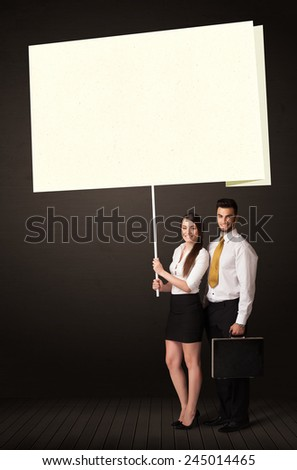 Young business couple holding a big, white post-it paper  - stock photo