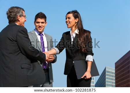 Young business couple shaking hands with partner outdoors. - stock photo