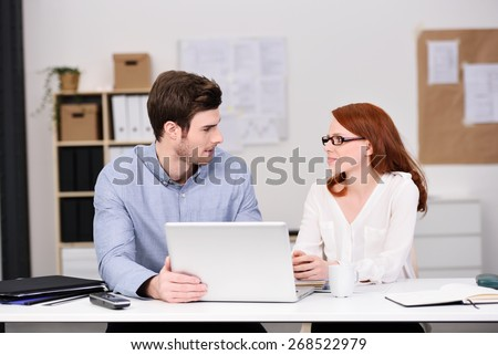 Young Business Couple Sitting at the Table with Laptop Computer and Looking Each Other Seriously - stock photo