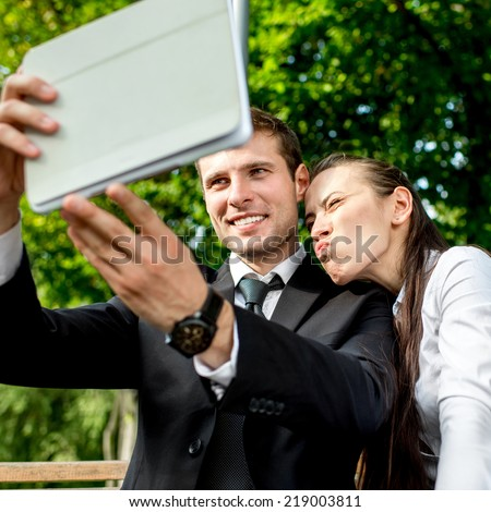 Young Business couple sitting on the bench and making selfie photo with tablets