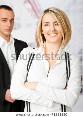 Young business couple - smiling woman and serious man in back, focus on female