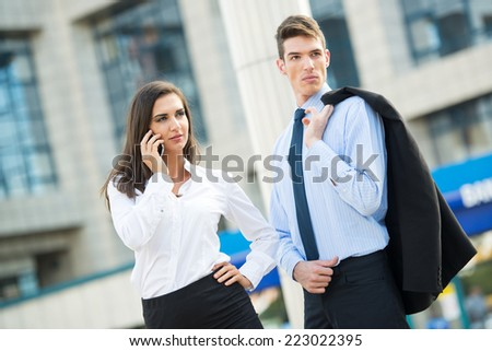 Young business couple standing in front of office buildings and business woman talking by mobile phone. - stock photo