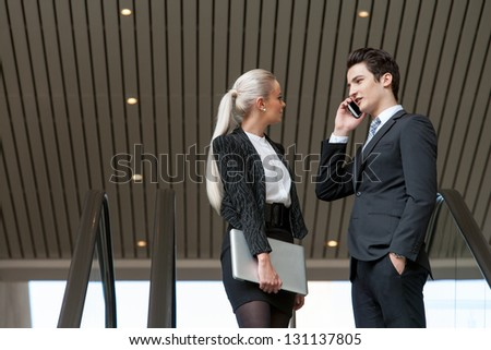 Young business couple talking on smart phone in mall. - stock photo