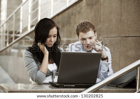 Young business couple  using laptop - stock photo